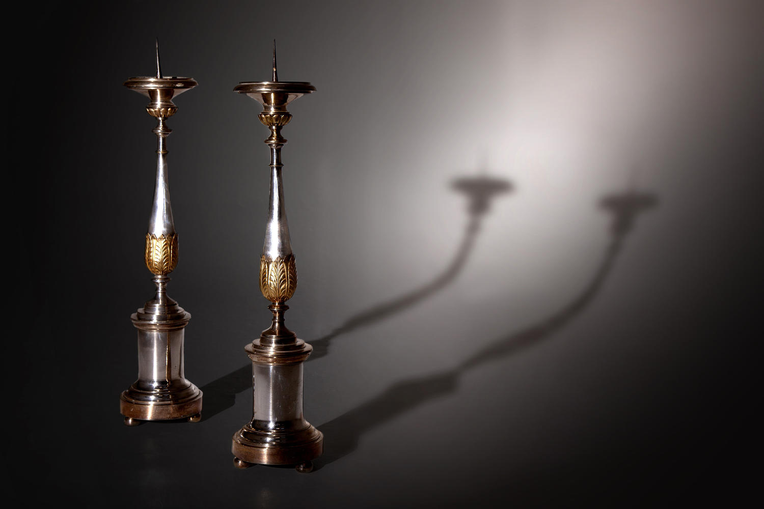 A tall pair of silvered and gilded pricket candlesticks